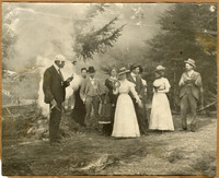 Group of men, women, and one girl stand near small bonfire in woods