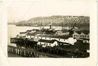 Pacific American Fisheries facilities  including Bellingham Canning Company with ships at dock in background and south hill of Bellingham in distance
