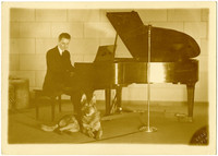 """Pianist Gunnar Anderson sits at a grand piano with German shepherd """"Duke"""" lying on floor at his feet"""