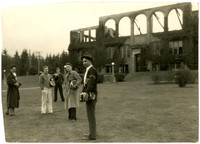 Five young men with school books stand on grass in front of burnt shell of Fairhaven High School, Bellingham, WA