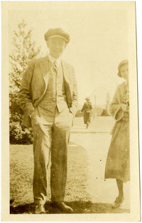A man in a snap-cap and matching suit poses with partially-seen woman in a park