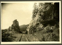 View of straight railroad tracks near Deming through a rock cut with forested hills in distance