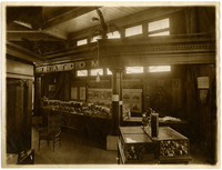 """Display of produce and products in """"Whatcom"""" booth made of heavy classical entablature and columns, at an exhibition hall"""
