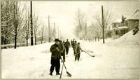Eleven unidentified men in a work crew shovelling snow
