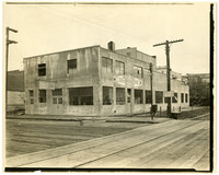Two-story concrete building fronts a wood-planked street with railroad tracks in foreground
