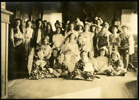 Large group of girls and young women pose in parlor, many in costume