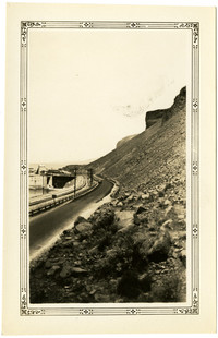 Steep, rocky slope of hillside next to highway running along Columbia River at Rock Island Dam