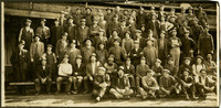 About seventy men pose in several rows on risers, most wearing work clothes, in front of warehouse or mill