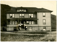"""Group of women pose on steps of four-story """"Edens Hall"""" dormitory at the State Normal School, Bellingham,WA"""