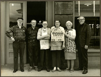 Four unidentified men and two women stand in a row in front of a doorway, possibly the Puget Sound Mail office