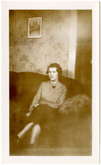 A young woman sits on a sofa