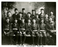 Fifteen men and one boy, all in Sehome volunteer firefighter uniform, and one man in suit, pose in three rows in studio portrait