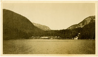 View from water of shoreline and cannery against forested hills