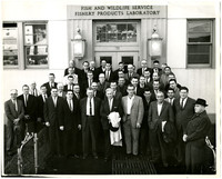 Large group of men in suits pose outside front doors of Fish and Wildlife Service Fishery Products Laboratory