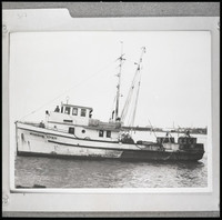 "The fishing boat ""Marsha Lynn"" sitting in the water with two crew visible on top of the pilot house"