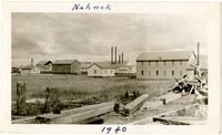 Multiple buildings of cannery facility of Naknek, Alaska, with fallen wooden beams and rubble in foreground