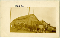 Horse-drawn wagon towing large steam boiler stands in front of Bellingham Livery & Transfer Co.