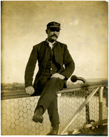 Uniformed man seated on railing