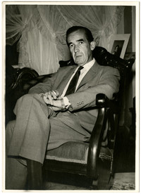 Edward R. Murrow seated in rocking chair in living room