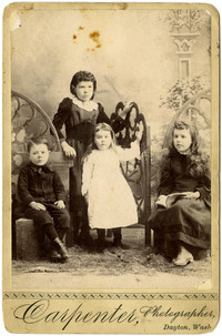 Four young children, three girls and a boy, pose in fine clthes for studio portrait