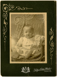 Studio portrait of seated child in christening gown