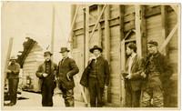 Six men standing outside King Cove warehouse