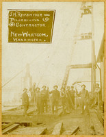 Ten men in workwear, several holding logging peaveys, stand on wooden platform in front of boom or other tall structure