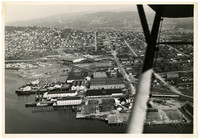 """Aerial view of the Pacific American Fisheries (PAF) complex in Fairhaven at the foot of Harris Avenue. Several buildings have """"P.A.F."""" painted in white on their roofs."""