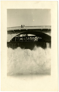 View from below the crashing water flowing over the dam, of two people standing on bridge over Whatcom creek on Dupont street, Bellingham, Washington
