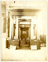 """Commercial display of classical columns and artifical doorway with stack of """"Crespo"""" cans in background and promotional signs for """"Wheeler Osgood Co."""" in front"""