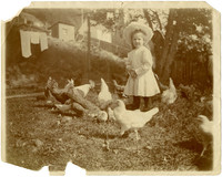 Young girl standing with flock of chickens