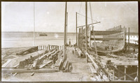 Shipyard with six men standing in and around ship under construction with bay of water in background, possibly Bellingham Bay
