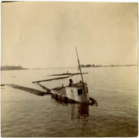 A partially sunken tugboat still attached to boomsticks of a log raft