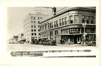 Exterior of Star Drug store on Elk (State) Street, Bellingham, WA, with early model cars parked on street, with the Herald Building background