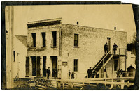 Exterior of T.G. Richards building, with several men standing lounging on adjacent boardwalk and staircase