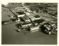 Aerial view of harbor, lagoon, industrial buildings, piers, ships at dry dock,and  raiilroad tracks diagonally bisecting the picture