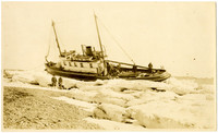 View from shore of fishing tender, the Warrior, beached in ice, tilting