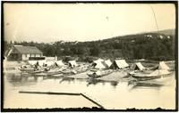 Canoes, tents, boat building, and repair shop at Native American fishing camp