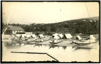 Canoes, tents, boat building, and repair shop at Native American fishing camp
