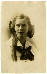 Studio portrait of unidentified young woman with hair tied in large bow