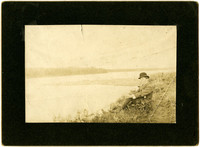 Man with pipe and hat sits on bluff overlooking water