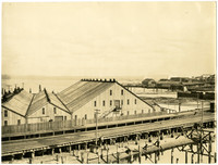 Large waterfront warehouses of Pacific American Fisheries at low tide, with sloped end of Taylor Avenue visible in upper right corner background