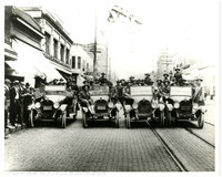 Four early model cars full of young soldiers in a line across cobblestone main street with onlookers to side