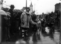 Man wearing native-Alaskan outfit standing with harnessed sled-dogs on street