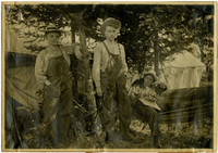 Young man and woman, both in overalls, next to woman in hammock
