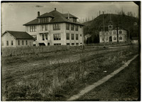 Burlington High School - a 3.5-story square building , seen from across a muddy road