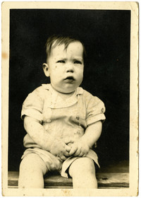 Unidentified infant sits on a wooden step