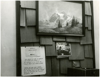 A grouping of photographs, notes, and large oil painting of Mount Shuksan hang on wall
