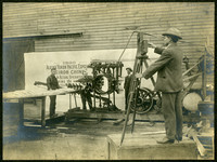 "Man in foreground stands on platform with camera on tripod to photograph the Smith Butchering machine, on display with ""1909 Alaska Yukon Pacific Exposition"" banner on wall in background"