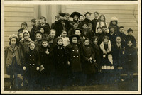 Approximately 30 young school children and several teachers bundled in winter coats pose outside schoolhouse